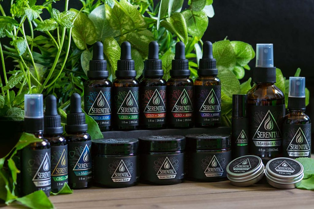 This is a group photo of most products in the Serenital line. Featured on a wood platform with green leaves in the background.